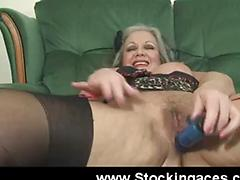 Mature lady fucks her pussy on the sofa