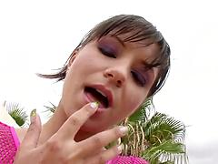 Model in a pink fishnet bonks herself with a pink sex toy outdoors